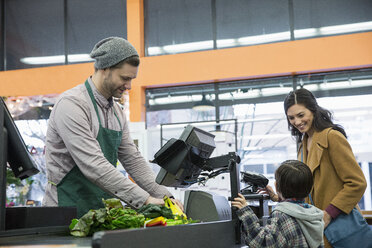 Worker making bill while standing with customer at counter in supermarket - CAVF33187