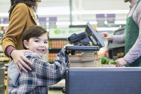 Portrait of boy standing with mother standing counter at supermarket - CAVF33190