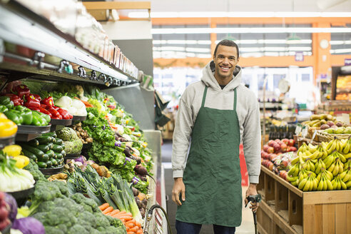 Portrait of smiling worker standing by shelves at supermarket - CAVF33199