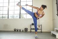 Confident female athlete exercising in health club - CAVF33268
