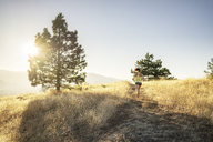 Rear view of woman jogging on mountain against clear sky during sunny day - CAVF33322