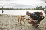 Side view of man stroking dog while crouching on sand at riverbank - CAVF33385