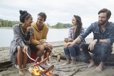 Happy friends roasting sausages while sitting at campfire against river - CAVF33424