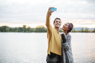 Friends taking selfie while standing by river against sky - CAVF33433