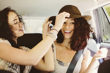 Happy female friends traveling in car - CAVF33448