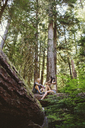 Low angle view of friends talking while sitting on log in forest - CAVF33454