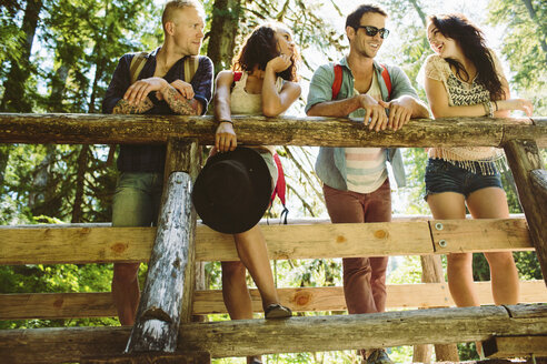 Low angle view of happy friends talking while standing on footbridge in forest - CAVF33460