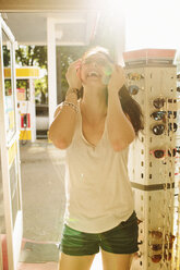 Cheerful woman trying sunglasses at gas station - CAVF33472