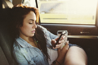 Woman with disposable cup using mobile phone while traveling in car - CAVF33475