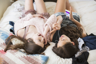 High angle view of happy female friends on bed at home - CAVF33478