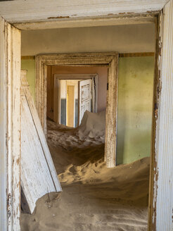 Africa, Namibia, inside a house of ghost town Kolmanskop, wooden doors and sand - RJ00756