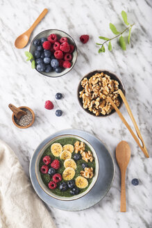 Buddha bowl of green chia pudding with slices of banana, blueberries, raspberries and walnuts - RTBF01141
