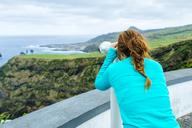 Azores, Sao Miguel, Woman looking through a tourist binoculars towards the sea - KIJF01913
