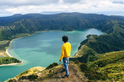 Azores, Sao Miguel, rear view of man looking at the Lagoa do Fogo - KIJF01919