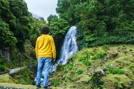 Azores, Sao Miguel, rear view of man looking at a waterfall in the Ribeira dos Caldeiroes Natural Park - KIJF01922