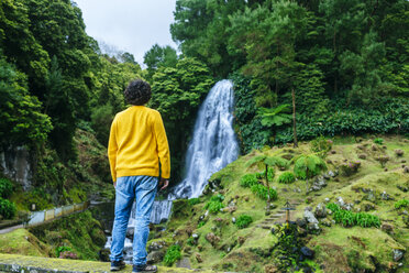 Azores, Sao Miguel, rear view of man looking at a waterfall in the Ribeira dos Caldeiroes Natural Park - KIJF01922