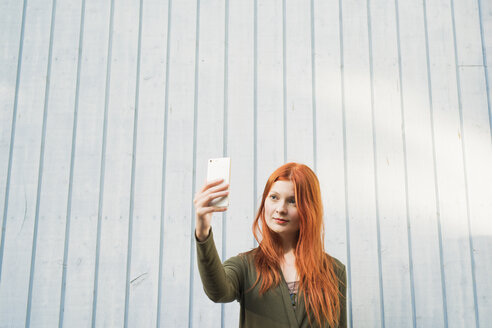 Redhaired woman taking selfie against white wall - FOLF06628