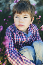 Boy sitting among pink flowers - FOLF06718