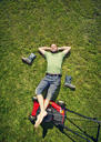 Man lying on grass with feet up on lawn mover in summer - FOLF06796