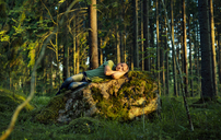 Man sleeping on moss covered rock in forest - FOLF06802