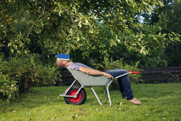 Man relaxing in wheelbarrow with book on his face - FOLF06805