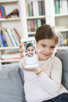Smiling girl showing selfie on cell phone display - LVF06850