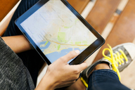 Close-up of woman holding tablet with digital street map - VABF01525