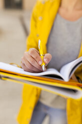 Close-up of woman taking notes outdoors - VABF01531