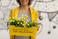 Close-up of smiling woman holding yellow spring flower box - VABF01537
