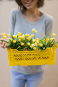 Close-up of happy woman holding yellow spring flower box - VABF01540
