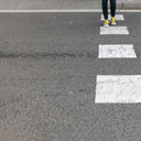Close-up of woman wearing sneakers crossing street - VABF01546