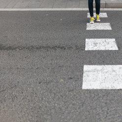 Close-up of woman wearing sneakers crossing street - VABF01546