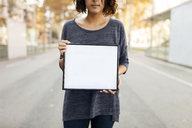 Close-up of woman holding blank frame on the street - VABF01549