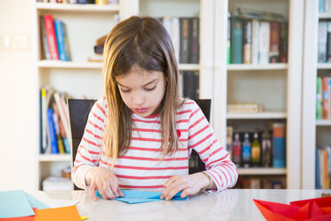Girl tinkering with paper on table at home - LVF06854