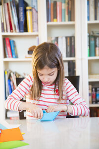 Girl tinkering with paper on table at home - LVF06857