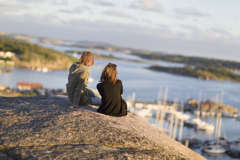 Mid adult women sitting on rock overlooking port and bay - FOLF07064