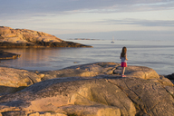 Girl standing on rocky seashore - FOLF07067