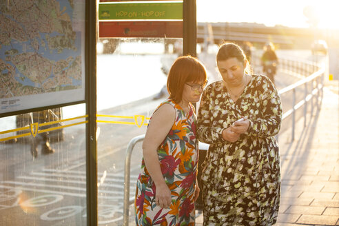 Woman with down syndrome standing by friend checking smart phone - FOLF07238