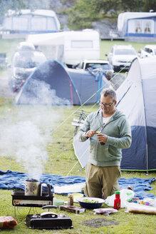 Mature man cooking at campsite - FOLF07301