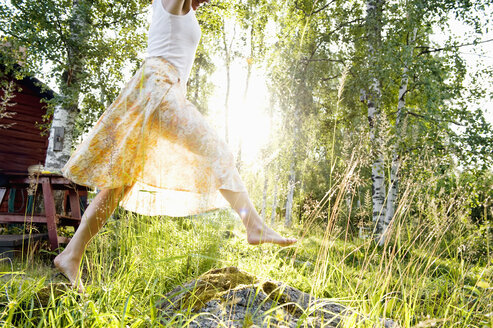 Young woman jumping in grass in backyard - FOLF07373