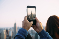 USA, New York City, man's hands taking a photo of Empire State Building with smartphone - GEMF01910