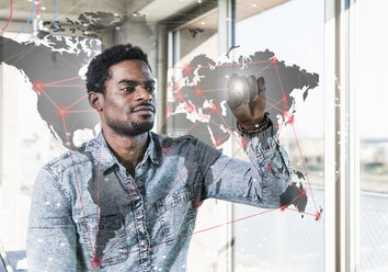 Casual businessman touching glass pane with world map in office - UUF13183