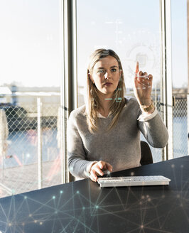 Young businesswoman touching projection screen with data in office - UUF13192