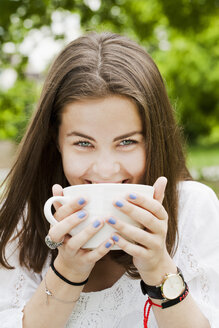Portrait of young woman drinking from cup in park - FOLF07614