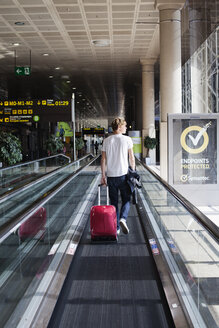 Man walking with pink wheeled suitcase in airport hall - FOLF07638