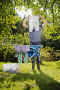Man holding laundry in front of his face - FOLF07806