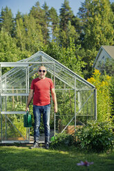 Man standing outside greenhouse and holding watering can - FOLF07809