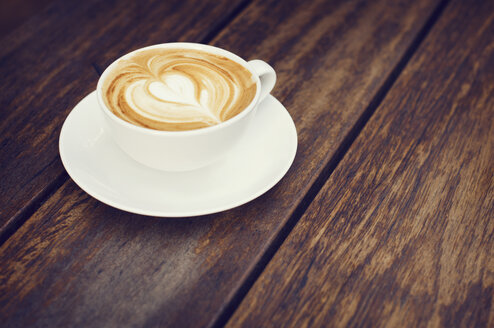 Close-up of coffee latte on wooden table at cafe - CAVF33579