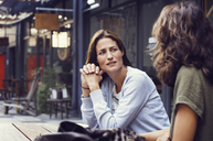 Mature woman talking to friend at sidewalk cafe - CAVF33582