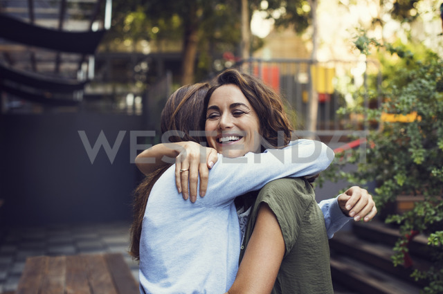 Affectionate mature women embracing at sidewalk cafe - CAVF33585